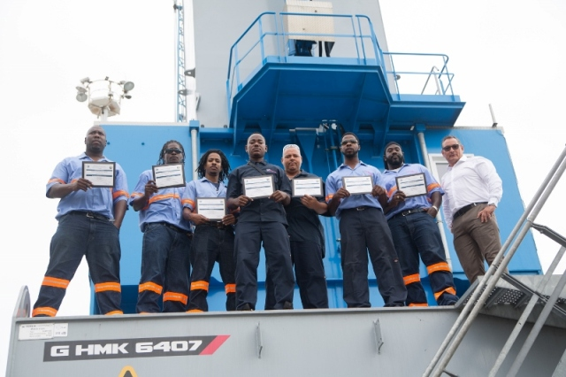 PHOTO CUTLINE: Romeo Gumbs along with colleagues at Port St. Maarten Cargo Operations work area.