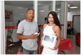 Caption: Carpenter, Jermaine  McLean, received a cup cake and a word of thanks from promo-girl Katherine, for being a TelEm Group customer in observance of World Telecommunication & Information  Society Day Wednesday, May 17th.