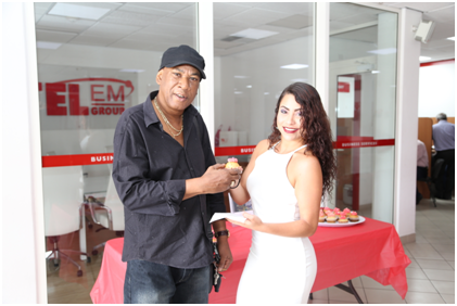Caption: Entertainer, Franklin Arrindell, marked World Telecommunication & Information Society Day Wednesday, May 17th, with a courtesy cup cake from promo-girl Katherine, when he stepped into the TelEm Group main building Wednesday morning.